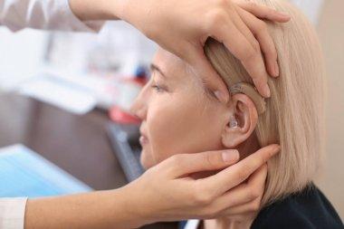 Otolaryngologist putting hearing aid in woman's ear in hospital