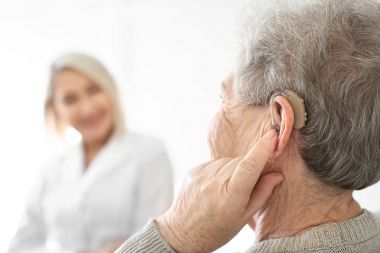 Senior woman adjusting hearing aid