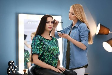 makeup artist working with model