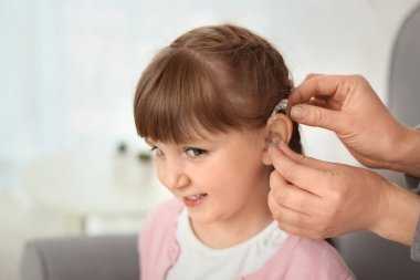 Doctor putting hearing aid in ear