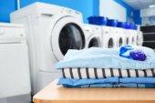 Fotografia Vestiti puliti con gel con perni in lavanderia self-service