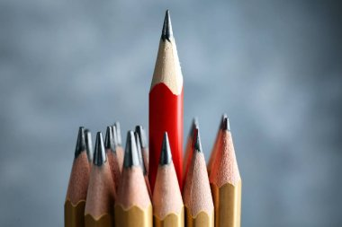 One red pencil among golden ones on blurred background. Difference and uniqueness concept