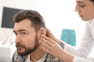 Otolaryngologist putting hearing aid in man's ear in hospital