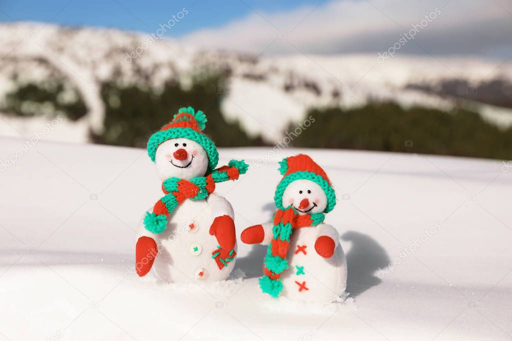 Two toy snowmen at mountain resort on sunny frosty day. Winter vacation