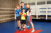Photo Little children with their trainer on boxing ring
