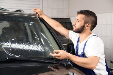Worker tinting car window