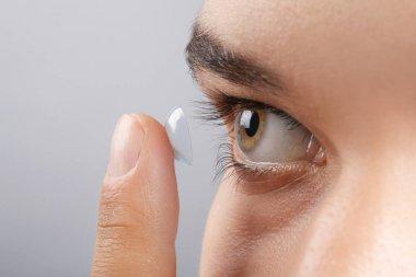 Young man putting contact lens
