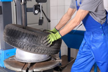 Professional mechanic using modern equipment to change tire in car service center