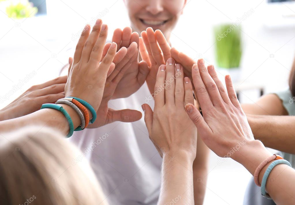 People putting hands together indoors. Unity concept
