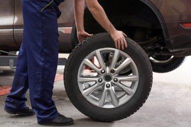 Mechanic with car wheel