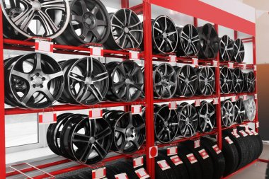 Shelves with alloy wheels and tires in modern car service centre