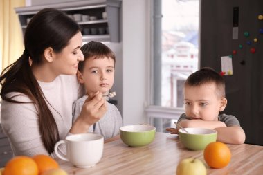Nanny feeding cute little boys in kitchen