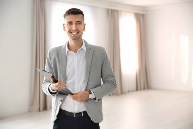 Portrait of real estate agent in empty apartment