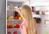 Mladá žena poblíž otevřené lednice v kuchyni
