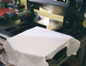 Fotografie Modern printing machine with t-shirt at workplace