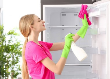 Woman cleaning refrigerator in kitchen