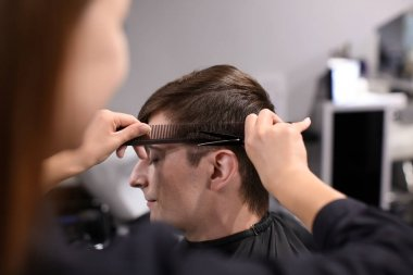 Professional stylist cutting client's hair in salon