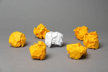 Crumpled paper balls and one different on grey background