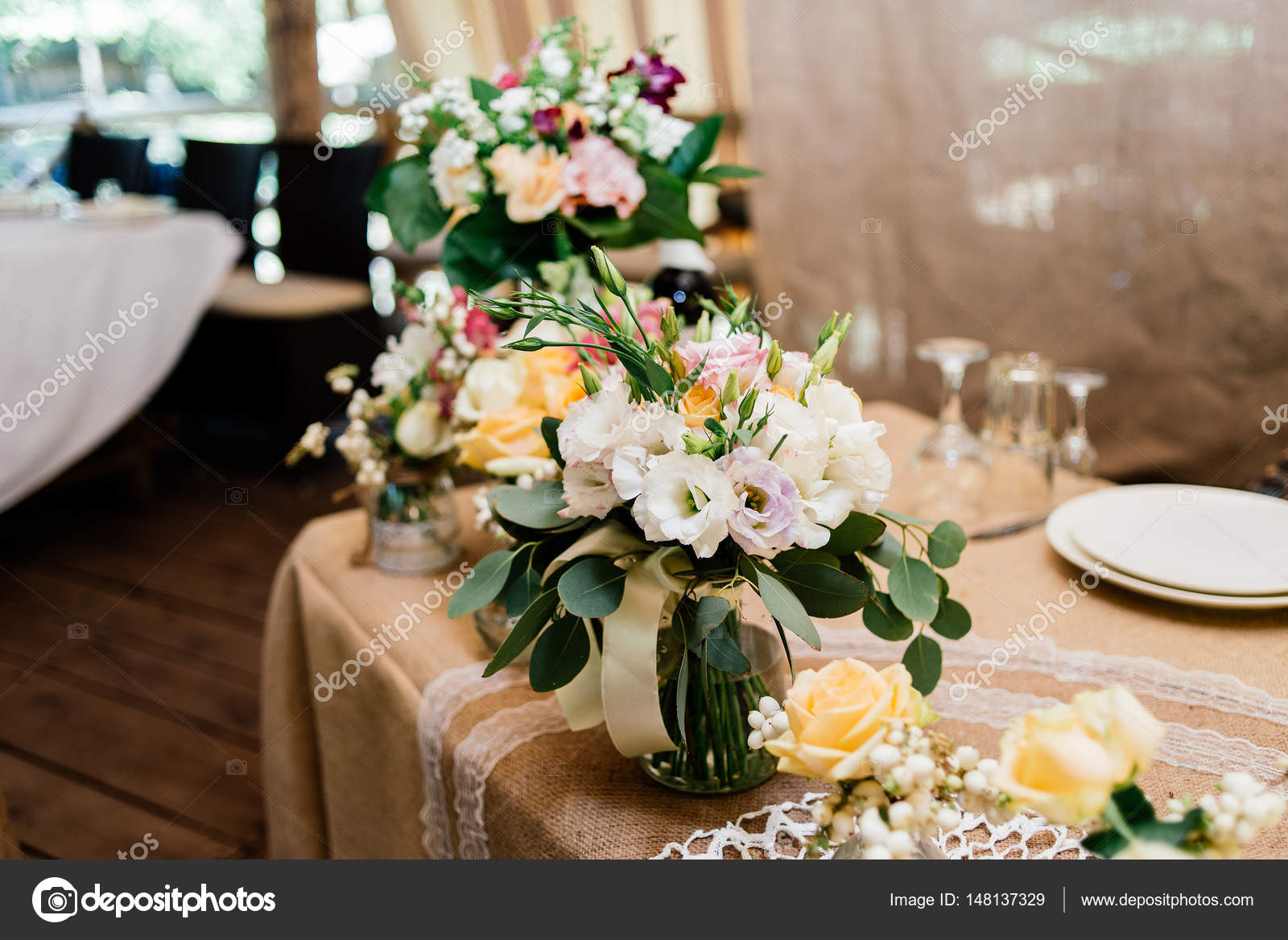 Wedding Bouquets Of Yellow White And Pink Roses Are In Vases