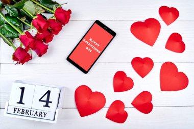 Sevgiliye arka plan ile buket kırmızı gül, cellphone ile işaret mutlu sevgililer günü, Kağıt kalpleri ve 14 Şubat ahşap blok takvim, kopya alanı. Tebrik kartı mockup. Üstten görünüm, düz yatıyordu