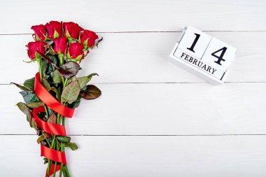 Sevgiliye arka plan ile şerit ve 14 Şubat ahşap blok takvim, kopya alanı ile kırmızı gül buketi. Tebrik kartı mockup. Aşk kavramı. Üstten Görünüm, düz yatıyordu