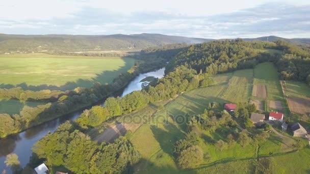 Letecký snímek lesy, zelené kopce a louky.