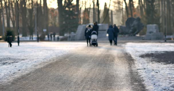 Unrecognizable people on the sidewalk in Warsaw.