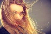 Attraktive blonde Frau mit vom Wind verwehten Haaren