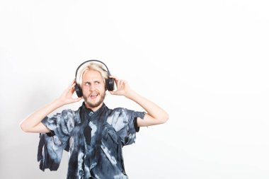 Cool guy having fun listens to music in headphones