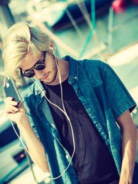 Blonde man in sunglasses listening to music
