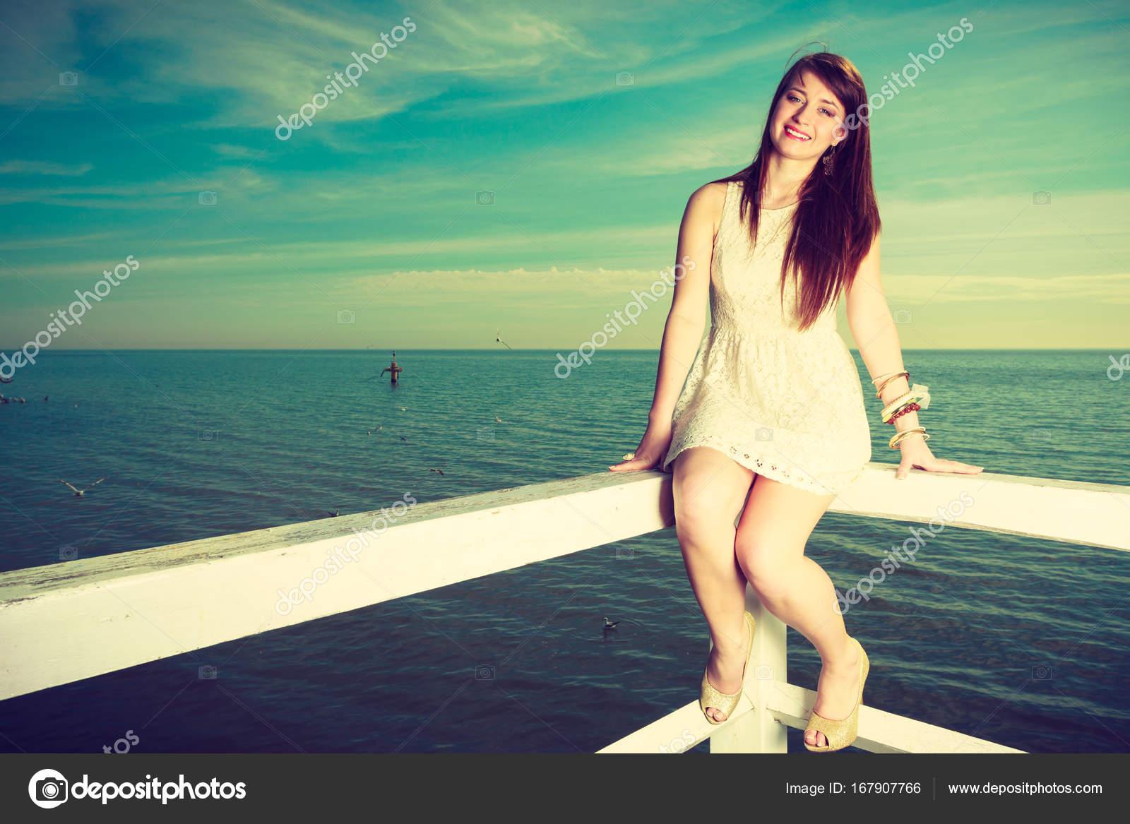 947713baa0f7 Γυναίκα με λευκό κοντό φόρεμα κάθεται στο εμπόδιο — Φωτογραφία Αρχείου