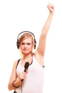 Woman singing to microphone wearing headphones
