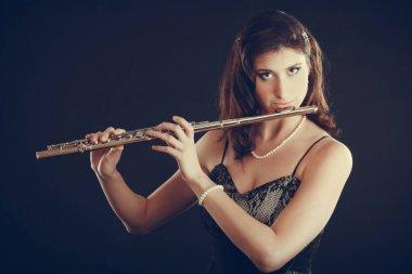 Woman playing transverse flute on black.