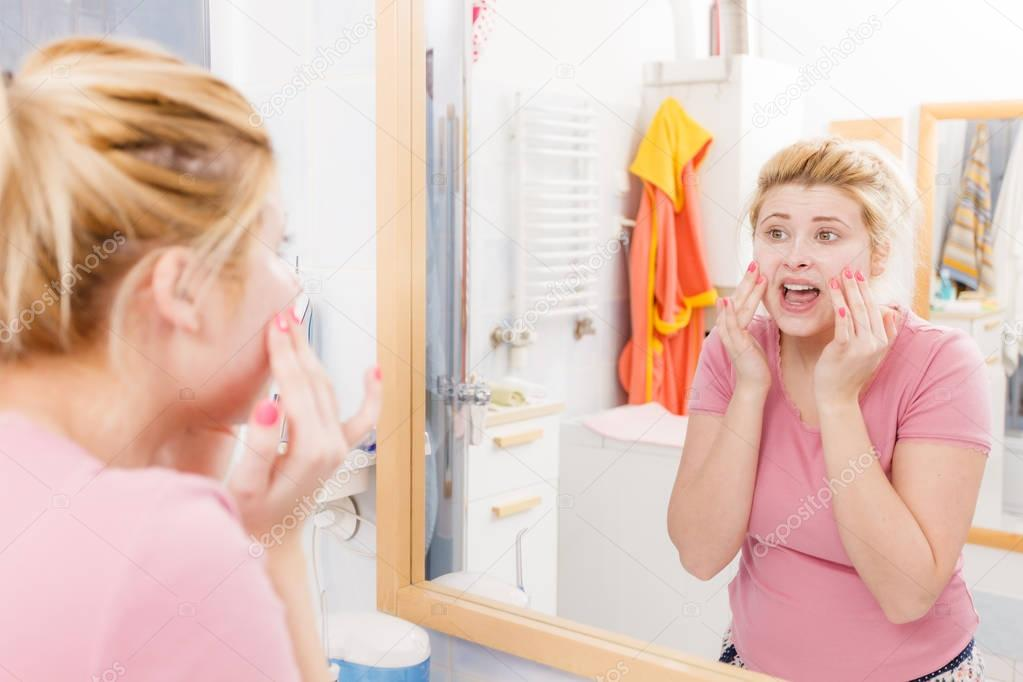 Sensitive, dry skin problems concept. Scared woman washing her face under sink.