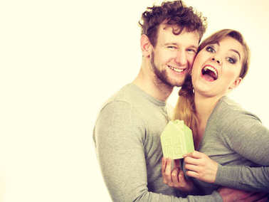 Cheerful couple together with building model