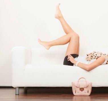 Fashionable girl with handbag lying on sofa