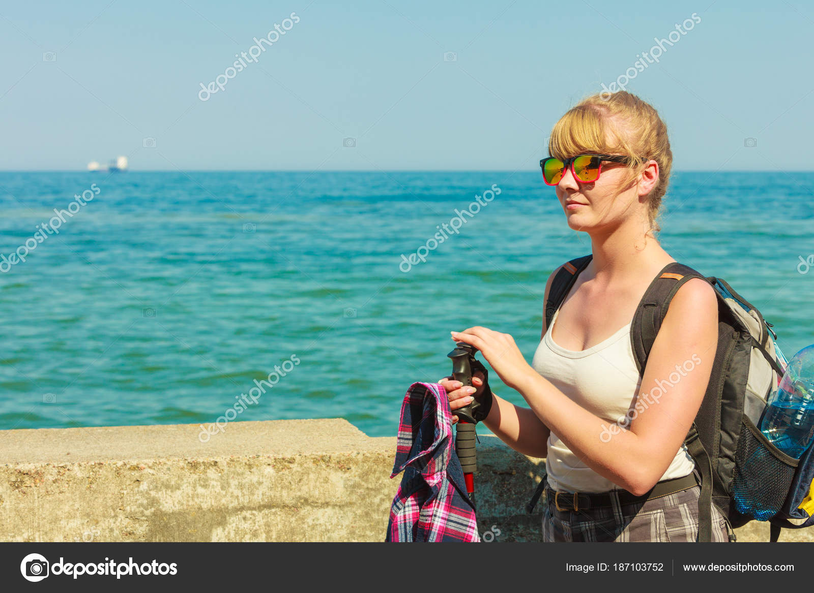young woman with backpack hiking on sea coast — Stock Photo ... a660147332f73