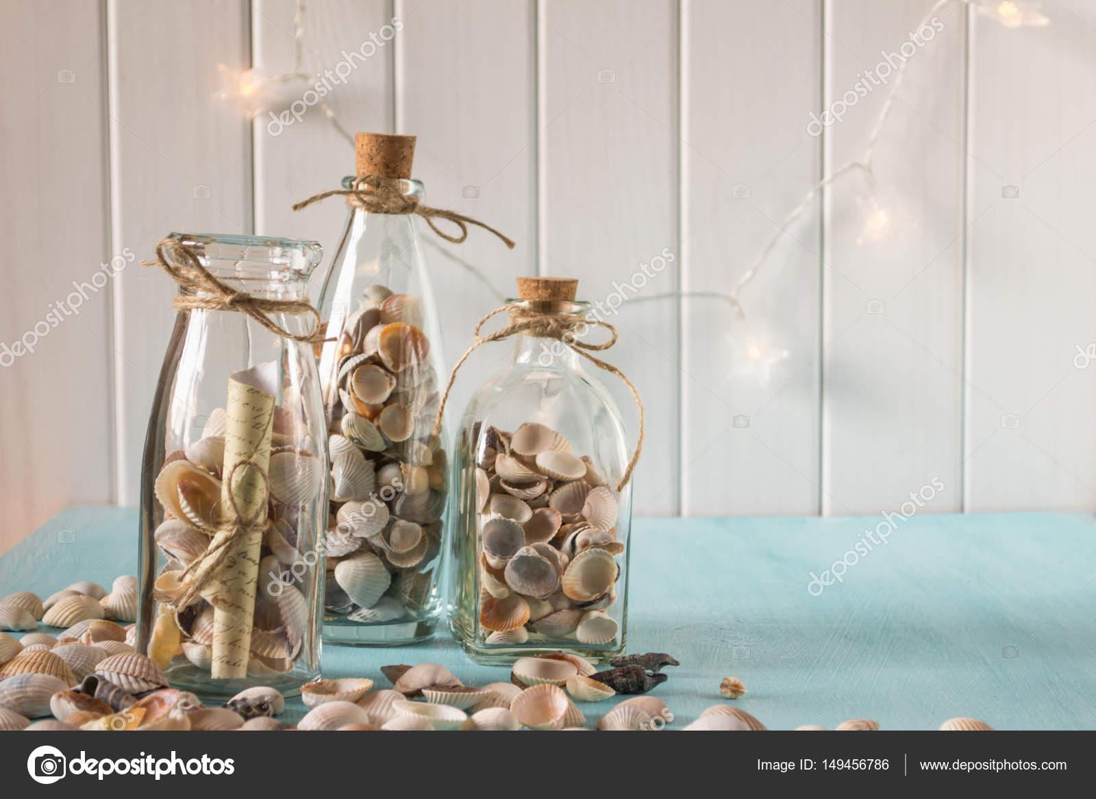 Idee van interieurdecoratie met schelpen en glazen flessen