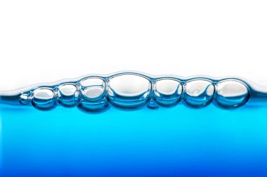 Close view of oxygen bubbles in clear blue water on white background