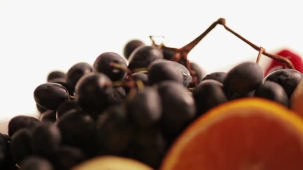 Fruits on a plate: grape, orange, lemon, kiwi, strawberry