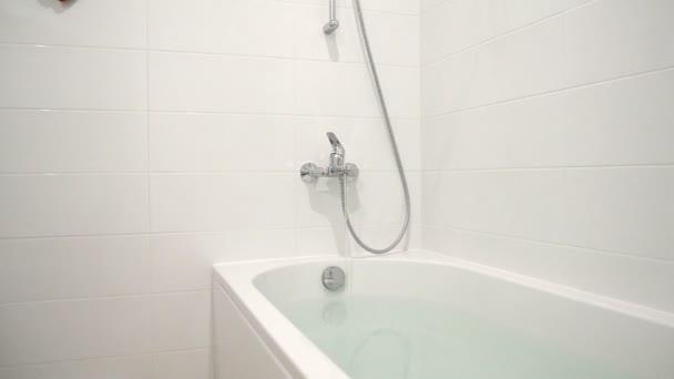 Detailní záběr z koupelny s vodou tekoucí z mixéru