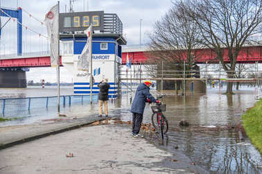 Duisburg , Germany - January 08 2017 : Lady surprised by the river Rhine flooding the promenade