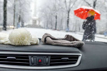 Conceptional winter shot of beanies in a car behind the front window while lady with red umbrella walks by