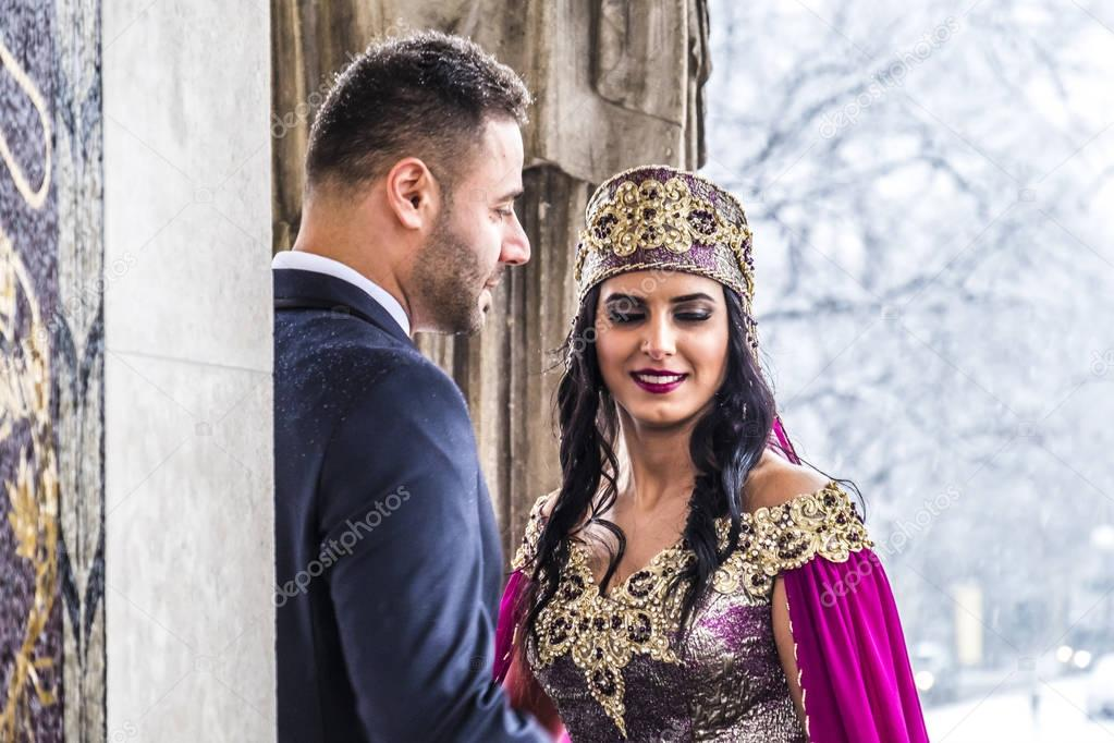 Happy couple in traditional turkish wedding dress during their wedding
