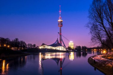 The skyline of Munich in Bavaria, Germany, with reflections in the lake and stars in the sky