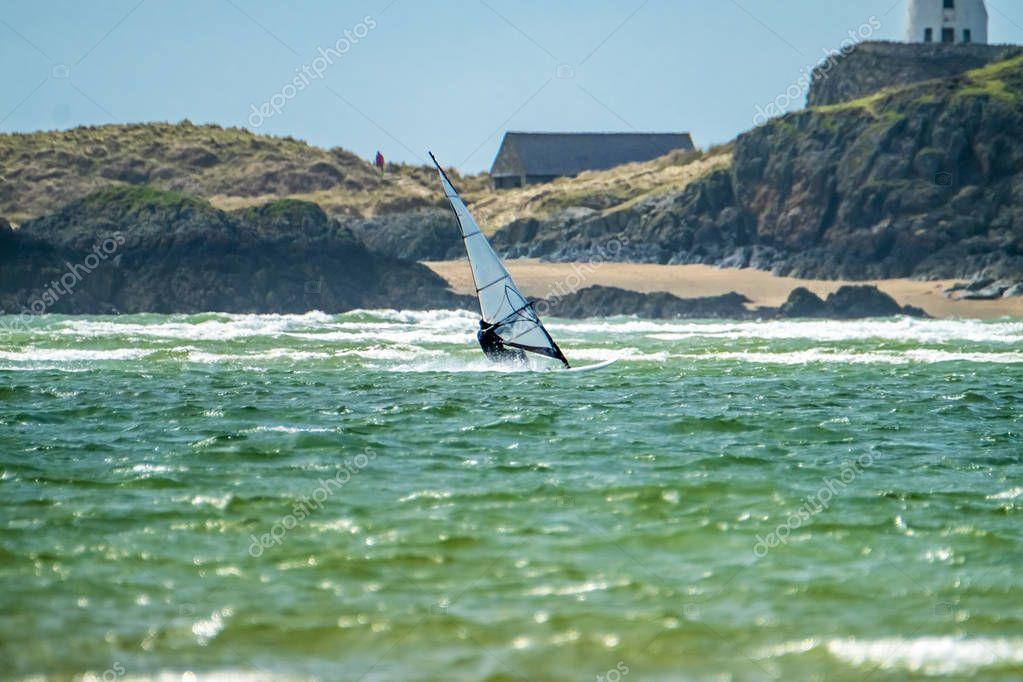 Wind surfer enjoys the beach at Newborough Warren with the Island of Llanddwyn in the background , Isle of Anglesey, North Wales, UK