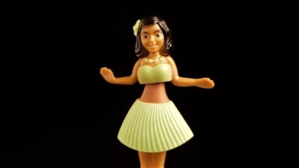 Traditionelle hawaiianische Hula-Tänzer-Puppe auf schwarzem Hintergrund