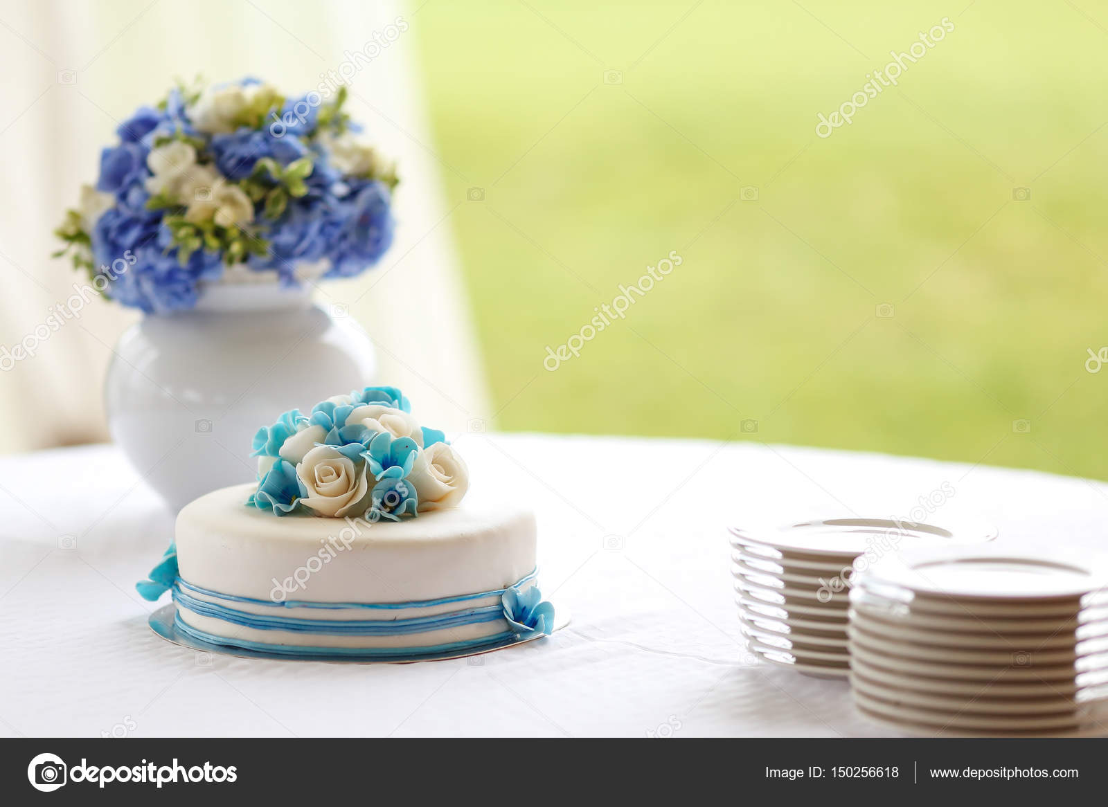 Wedding decoration with a cake and a vase with blue and white ...