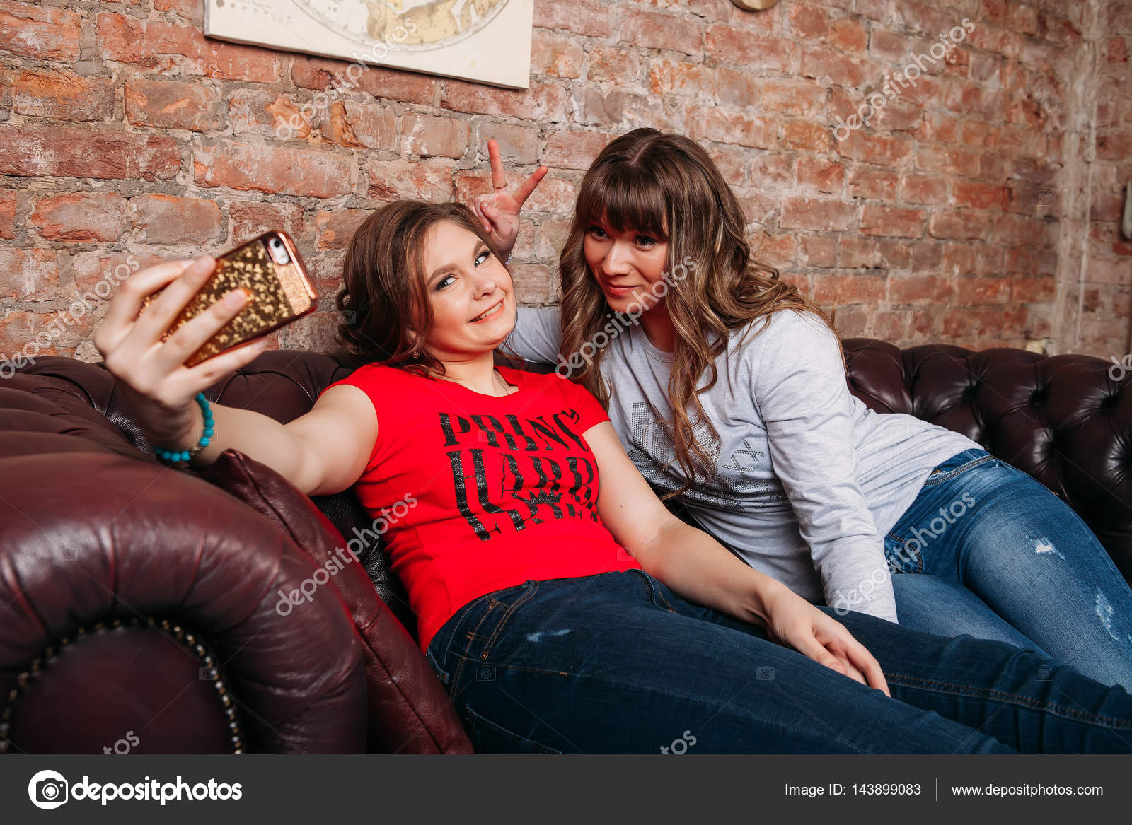 Zwei junge schöne fröhliche Freundinnen in Blue Jeans sitzt ...