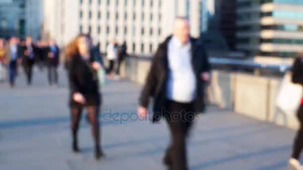 Defocussed time-lapse of commuters on London Bridge.